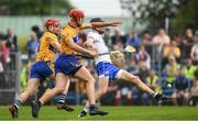 27 May 2018; Waterford full back Barry Coughlan kicks the sliothar, out for a '65', under pressure from Peter Duggan and John Conlon of Clare, 11, during the Munster GAA Hurling Senior Championship Round 2 match between Clare and Waterford at Cusack Park in Ennis, Co Clare. Photo by Ray McManus/Sportsfile