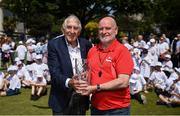 """31 May 2018; Ronnie Delany was guest of honour at his alma mater, CUS Sports Day at College Park, Trinity College. CUS Junior School on Leeson Street is celebrating 150 years of the school. Teachers and children also joined to celebrate the 62nd anniversary of when Ronnie Delany became the first Irish man to break 4 minutes for the mile in Compton, USA, running 3:59.0 on June 1st, 1956, the same year he won gold over 1500m at the Olympic Games in Melbourne. Pictured is Cyril Smyth, right, Trinity College, making a presentation to Ronnie Delany during The Ronnie Delany """"Smile Run"""", at College Park, Trinity College, Dublin. Photo by David Fitzgerald/Sportsfile"""