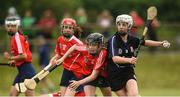 10 June 2018; Katlyn Sheehan of Sarsfields, Co Cork, in action against Ava Killian of Carnmore, Co Galway, during the Division 1 Camogie semi-final between Carnmore, Co Galway, and Sarsfields, Co Cork, at the John West Féile na nGael national competition which took place this weekend across Connacht, Westmeath and Longford. This is the third year that the Féile na nGael and Féile Peile na nÓg have been sponsored by John West, one of the world's leading suppliers of fish. The competition gives up-and-coming GAA superstars the chance to participate and play in their respective Féile tournament, at a level which suits their age, skills and strengths. Photo by Matt Browne/Sportsfile
