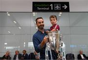 17 August 2018; Darragh Madden, from Oranmore, Co Galway, with his son Conor, age 2, with the Liam MacCarthy Cup at the GAA Fáilte Abhaile event at Dublin Airport in Dublin. Photo by Piaras Ó Mídheach/Sportsfile