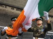 """Ag ardú. Members of the Irish Defence Forces Sergeant Brian Harte, right, and Sergeant Ian Jones raise the Tricolour at Croke Park on the morning of the All-Ireland hurling final.    This image may be reproduced free of charge when used in conjunction with a review of the book """"A Season of Sundays 2018"""". All other usage © SPORTSFILE"""