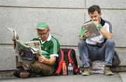 """Studying form. Two early-bird Limerick supporters review the Sunday papers before their team does battle on All-Ireland hurling final day.      This image may be reproduced free of charge when used in conjunction with a review of the book """"A Season of Sundays 2018"""". All other usage © SPORTSFILE"""
