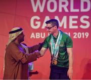 17 March 2019; Team Ireland's Patrick Quinlivan, a member of the Salto SOC from Letterkenny, Co. Donegal, receives the third of his seven medals for Artistic Gymnastics from H.H. Abdulla Bin Mohomed Al Hamed on Day Three of the 2019 Special Olympics World Games in the Abu Dhabi National Exhibition Centre, Abu Dhabi, United Arab Emirates. Photo by Ray McManus/Sportsfile