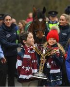 7 April 2019; Zack, left, and Tiana O'Leary, children of owner Michael O'Leary with the cup as the winner of the 2019 Randox Health Aintree Grand National Tiger Roll is led through the village of Summerhill in County Meath by grooms Karen Morgan, left, and Louise Dunne. Photo by Harry Murphy/Sportsfile