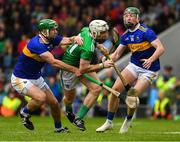 16 June 2019; Cian Lynch of Limerick on his way to score the last point of the game under pressure from Noel McGrath, left, and Robert Byrne of Tipperary during the Munster GAA Hurling Senior Championship Round 5 match between Tipperary and Limerick in Semple Stadium in Thurles, Tipperary. Photo by Ray McManus/Sportsfile
