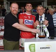 18 July 2019; Cork captain Peter O'Driscoll is presented with the cup by EirGrid Community Officer Eoghan O'Sullivan, left, and Munster Council Chairman Liam Lenihan following the EirGrid Munster GAA Football U20 Championship Final match between Cork and Kerry at Páirc Ui Rinn in Cork. Photo by Matt Browne/Sportsfile