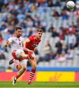 20 July 2019; Matthew Donnelly of Tyrone kicks a point despite Ian Magure of Cork during the GAA Football All-Ireland Senior Championship Quarter-Final Group 2 Phase 2 match between Cork and Tyrone at Croke Park in Dublin. Photo by David Fitzgerald/Sportsfile