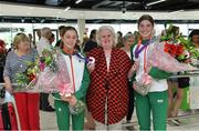 22 July 2019; Sarah Healy, silver medal winner from the Women's 1500m event, left, and Kate O'Connor, silver medal winner from the Women's Heptathlon event, are presented with flowers by President of Athletics Ireland Georgina Drumm on the return home of Team Ireland from the European Athletics U20 Athletics Championships at Dublin Airport. Photo by Piaras Ó Mídheach/Sportsfile