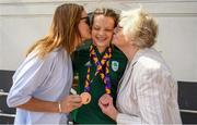 29 July 2019; Molly Mayne of Ireland with her 100m and 200m breaststroke Bronze medals recieves kisses from Mother Laura Mayne and Grandmother Maureen Kissanne on Team Ireland's return to Dublin Airport in Dublin from the 2019 Summer European Youth Olympic Festival in Baku. Photo by Harry Murphy/Sportsfile