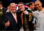 3 August 2019; Michael Conlan, centre, celebrates victory with trainer Adam Booth, right, and Bob Arum, CEO of TopRank, after defeating Diego Alberto Ruiz during their WBA and WBO Inter-Continental Featherweight title bout at Falls Park in Belfast. Photo by Ramsey Cardy/Sportsfile