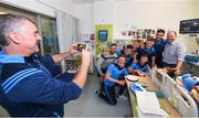 19 August 2019; Tipperary manager Liam Sheedy takes a photograph of Charlie Aabo, and his son Kian Barnes-Aabo, aged 5, from Glanmire, Co. Cork, with Tipperary players on a visit by the Tipperary All-Ireland hurling champions to Children's Health Ireland at Crumlin in Dublin.  Photo by Sam Barnes/Sportsfile