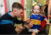 19 August 2019; Holly Carroll, aged 4, from Clonmel, Co. Tipperary, has her jersey signed by Paddy Cadell of Tipperary on a visit by the Tipperary All-Ireland hurling champions to Children's Health Ireland at Crumlin in Dublin.  Photo by Sam Barnes/Sportsfile