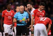 15 October 2019; Referee Szymon Marciniak issues Shane Duffy of Republic of Ireland with a yellow card during the UEFA EURO2020 Qualifier match between Switzerland and Republic of Ireland at Stade de Genève in Geneva, Switzerland. Photo by Stephen McCarthy/Sportsfile