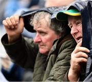 """23 June 2019; Meath supporters Matt Grimes, from Dundalk, Co Louth and Noel Clarke, right, from Simonstown GAA Club, Co Meath, take shelter during the Leinster GAA Football Senior Championship Final match between Dublin and Meath at Croke Park in Dublin. Photo by Ray McManus/Sportsfile This image may be reproduced free of charge when used in conjunction with a review of the book """"A Season of Sundays 2019"""". All other usage © SPORTSFILE"""