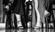 16 November 2019; (EDITOR'S NOTE: Image has been converted to black & white) A tattoo is seen on the foot of Monica McGuirk of Meath sitting alongside Sinead Burke of Galway during the TG4 All-Ireland Ladies Football All Stars Awards banquet, in association with Lidl, at the Citywest Hotel in Saggart, Dublin. Photo by Brendan Moran/Sportsfile