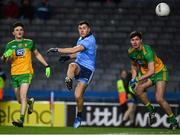 22 February 2020; Colm Basquel of Dublin kicks a score to level the game despite the efforts of Niall O'Donnell, left, and Brendan McCole of Donegal during the Allianz Football League Division 1 Round 4 match between Dublin and Donegal at Croke Park in Dublin. Photo by Sam Barnes/Sportsfile