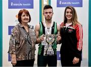 1 March 2020; Dean Adams of Ballymena and Antrim AC, is presented with the Craig Lynch cup by Craig's mother Anne Lynch, left, and fiancé Amy Cotter, right, after winning the Senior Men's 60m event during Day Two of the Irish Life Health National Senior Indoor Athletics Championships at the National Indoor Arena in Abbotstown in Dublin. Photo by Sam Barnes/Sportsfile