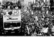 1 July 1990; The Republic of Ireland squad are cheered by supporters as they are brought by open top bus from Dublin Airport to College Green in Dublin city centre on their arrival home for a homecoming reception after their participation in the 1990 FIFA World Cup Finals in Italy. Photo by Ray McManus/Sportsfile