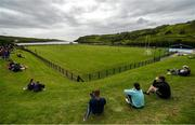 18 July 2020; Spectators watch from the bank overlooking the pitch during the Donegal County Divisional League Division 1 Section B match between Kilcar and Killybegs at Towney Park in Kilcar, Donegal. Competitive GAA matches have been approved to return following the guidelines of Phase 3 of the Irish Government's Roadmap for Reopening of Society and Business and protocols set down by the GAA governing authorities. With games having been suspended since March, competitive games can take place with updated protocols including a limit of 200 individuals at any one outdoor event, including players, officials and a limited number of spectators, with social distancing, hand sanitisation and face masks being worn by those in attendance among other measures in an effort to contain the spread of the Coronavirus (COVID-19) pandemic. Photo by Seb Daly/Sportsfile