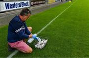 17 July 2020; St Martin's kitman Mick Reade sanitises the sliotars prior the Wexford County Senior Hurling Championship Group A Round 1 match between Oulart the Ballagh and St Martin's at Chadwicks Wexford Park in Wexford. Competitive GAA matches have been approved to return following the guidelines of Phase 3 of the Irish Government's Roadmap for Reopening of Society and Business and protocols set down by the GAA governing authorities. With games having been suspended since March, competitive games can take place with updated protocols including a limit of 200 individuals at any one outdoor event, including players, officials and a limited number of spectators, with social distancing, hand sanitisation and face masks being worn by those in attendance among other measures in an effort to contain the spread of the Coronavirus (COVID-19) pandemic. Photo by Brendan Moran/Sportsfile