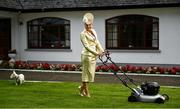 30 July 2020; Louise Allen from Slane in Meath, and her dog Sambo, cuts the grass in her outfit for the 2020 Galway Races Ladies' Day, which has now had to go virtual / online due to horse racing continuing behind closed doors on the advice of the Irish Government in an effort to contain the spread of the Coronavirus. Photo by Harry Murphy/Sportsfile