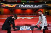 29 October 2020; Darragh Walsh, left, and team videographer Shane Taaffe hang out a banner in commemoration to the late Dundalk team videographer Harry Taaffe prior to the UEFA Europa League Group B match between Arsenal and Dundalk at the Emirates Stadium in London, England. Photo by Ben McShane/Sportsfile