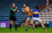 1 November 2020; Gary Brennan of Clare gets away from Robbie Kiely of Tipperary and referee Conor Lane during the Munster GAA Football Senior Championship Quarter-Final match between Tipperary and Clare at Semple Stadium in Thurles, Tipperary. Photo by Diarmuid Greene/Sportsfile