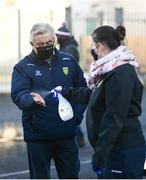22 November 2020; Geraldine McCavanagh sanitizes the hands of Donegal county board Chairman Mick McGrath arrives prior to the Ulster GAA Football Senior Championship Final match between Cavan and Donegal at Athletic Grounds in Armagh. Photo by David Fitzgerald/Sportsfile