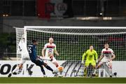10 December 2020; Ainsley Maitland-Niles of Arsenal has a shot on goal despite the tackle of Sean Gannon, left, of Dundalk during the UEFA Europa League Group B match between Dundalk and Arsenal at the Aviva Stadium in Dublin. Photo by Ben McShane/Sportsfile