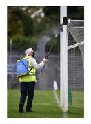 """12 September 2020; Taking no chances. Martin Keane sanitises the goalposts during half-time at Cusack Park in Ennis, one of thousands of GAA officials adhering to the health guidelines in order to ensure players' safety. Photo by Ray McManus/Sportsfile This image may be reproduced free of charge when used in conjunction with a review of the book """"A Season of Sundays 2020"""". All other usage © Sportsfile"""