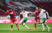 30 March 2021; Robbie Brady of Republic of Ireland has a shot on goal despite the attention of Boualem Khoukhi of Qatar during the international friendly match between Qatar and Republic of Ireland at Nagyerdei Stadion in Debrecen, Hungary. Photo by Stephen McCarthy/Sportsfile