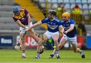 9 May 2021; Kevin Foley of Wexford clears the sliotar under pressure of PJ Scully and Charlie Dwyer of Laois during the Allianz Hurling League Division 1 Group B Round 1 match between Wexford and Laois at Chadwicks Wexford Park in Wexford. Photo by Brendan Moran/Sportsfile