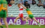 11 July 2021; Conor Glass of Derry kicks a point despite the attention of Eoghan Ban Gallagher of Donegal during the Ulster GAA Football Senior Championship Quarter-Final match between Derry and Donegal at Páirc MacCumhaill in Ballybofey, Donegal. Photo by Stephen McCarthy/Sportsfile