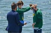 29 July 2021; Paul O'Donovan of Ireland, right, is presented with his gold medal by team-mate Fintan McCarthy after winning the Men's Lightweight Double Sculls final at the Sea Forest Waterway during the 2020 Tokyo Summer Olympic Games in Tokyo, Japan. Photo by Brendan Moran/Sportsfile