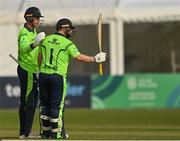 1 September 2021; Paul Stirling of Ireland raises his bat and is congratulated by team-mate Shane Getkate after reaching 100 runs during match three of the Dafanews T20 series between Ireland and Zimbabwe at Bready Cricket Club in Magheramason, Tyrone. Photo by Harry Murphy/Sportsfile