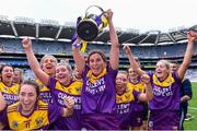 12 September 2021; Aisling Halligan of Wexford, centre, holds the cup aloft after her side's victory in the All-Ireland Premier Junior Camogie Championship Final match between Armagh and Wexford at Croke Park in Dublin. Photo by Piaras Ó Mídheach/Sportsfile