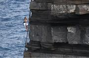 12 September 2021; Antonina Vyshyvanova of Ukraine climbs up the cliff on a ladder following her dive during round four of the Red Bull Cliff Diving World Series at Downpatrick Head in Mayo. Photo by Ramsey Cardy/Sportsfile