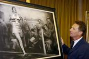 3 June 2004; Former Irish athlete Eamonn Coghlan admires a framed charcoal drawing of the famous moment when athlete Roger Bannister became the first person to run a mile in under four minutes. The Westbury Hotel, Dublin. Picture credit; Brian Lawless / SPORTSFILE