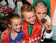 16 August 2013; Men's 50k walk gold medal winner Robert Heffernan with children Cathal, age 8, and Meghan, age 10, in Dublin airport on his return from the IAAF World Athletics Championships in Moscow. Dublin Airport, Dublin. Picture credit: Paul Mohan / SPORTSFILE