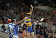 26 June 2004; Tony Griffin, Clare, fields a high ball against Paul Cuddy, Laois, as team-mate Michael McEvoy, 7, awaits the breaking ball. Guinness Senior Hurling Championship Qualifier, Round 1, Clare v Laois, Gaelic Grounds, Limerick. Picture credit; Pat Murphy / SPORTSFILE