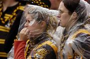 12 September 2004; Kilkenny fans shelter from the rain during the final stages of the game. Guinness All-Ireland Senior Hurling Championship Final, Cork v Kilkenny, Croke Park, Dublin. Picture credit; Ray McManus / SPORTSFILE *** Local Caption *** Any photograph taken by SPORTSFILE during, or in connection with, the 2004 Guinness All-Ireland Hurling Final which displays GAA logos or contains an image or part of an image of any GAA intellectual property, or, which contains images of a GAA player/players in their playing uniforms, may only be used for editorial and non-advertising purposes.  Use of photographs for advertising, as posters or for purchase separately is strictly prohibited unless prior written approval has been obtained from the Gaelic Athletic Association.