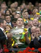 26 September 2004; President of the GAA Sean Kelly presents the Sam Maguire cup to Kerry captain Dara O Cinneide. Bank of Ireland All-Ireland Senior Football Championship Final, Kerry v Mayo, Croke Park, Dublin. Picture credit; Brendan Moran / SPORTSFILE *** Local Caption *** Any photograph taken by SPORTSFILE during, or in connection with, the 2004 Bank of Ireland All-Ireland Senior Football Final which displays GAA logos or contains an image or part of an image of any GAA intellectual property, or, which contains images of a GAA player/players in their playing uniforms, may only be used for editorial and non-advertising purposes.  Use of photographs for advertising, as posters or for purchase separately is strictly prohibited unless prior written approval has been obtained from the Gaelic Athletic Association.