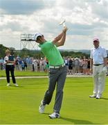 18 June 2014; Rory McIlroy, watched by playing partner Dermot Desmond, after hitting a golf ball with a hurley on the 9th fairway during the 2014 Irish Open Golf Championship Pro-Am. Fota Island, Cork. Picture credit: Diarmuid Greene / SPORTSFILE