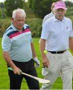 18 June 2014; Gerry McIlroy, father of Rory McIlroy, watched by playing partner Dermot Desmond, plays with a golf ball and hurley on the 9th fairway during the 2014 Irish Open Golf Championship Pro-Am. Fota Island, Cork. Picture credit: Diarmuid Greene / SPORTSFILE