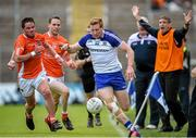 28 June 2014; Kieran Hughes, Monaghan, keeps the ball in play as he is pursued by Eugene McVerry and Finnian Moriarty, Armagh, as Armagh assistant manager Kieran McGeeney appeals for a sideline ball. Ulster GAA Football Senior Championship, Semi-Final, Armagh v Monaghan, St Tiernach's Park, Clones, Co. Monaghan. Picture credit: Brendan Moran / SPORTSFILE
