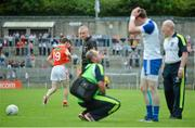 6 July 2014; Finnian Moriarty, left, Armagh, leaves the field after picking up a black card for a foul on Conor McManus, Monaghan, receiving treatment in the foreground. Ulster GAA Football Senior Championship, Semi-Final Replay, Armagh v Monaghan, St Tiernach's Park, Clones, Co. Monaghan. Picture credit: Piaras Ó Mídheach / SPORTSFILE