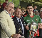 13 July 2014; Kevin Molloy, left, from Electric Ireland, proud sponsor of the GAA All-Ireland Minor Championships, presents Mayo captain Cian Hanley, with the Connacht GAA Football Minor Championship trophy, pictured, centre, is former GAA President Dr. Mick Loftus. Electric Ireland Cup Presentation at Connacht GAA Football Minor Championship Final, Mayo v Roscommon, Elverys MacHale Park, Castlebar, Co. Mayo. Picture credit: David Maher / SPORTSFILE