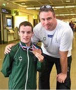 11 August 2014; The Allianz Irish Paralympic Swim team on their return home from the 2014 Paralympic Swimming (IPC) European Championship in Eindhoven, where they won two bronze medals, and recorded six personal best and six season's best times. Pictured is double bronze medalist James Scully, from Ratoath, Co. Meath, with Dave Malone, Performance Manager, Paralympics Ireland. 2014 IPC Swimming European Championships Paralympic Swimmers Return from 2014 IPC Swimming European Championships, Dublin Airport, Dublin. Picture credit: Ramsey Cardy / SPORTSFILE