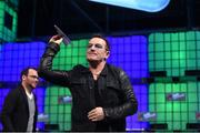 6 November 2014; Bono, Musician, Elevation Partners, returns a paper airplane to the crowd on the centre stage during Day 3 of the 2014 Web Summit in the RDS, Dublin, Ireland. Picture credit: Stephen McCarthy / SPORTSFILE / Web Summit