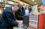 12 November 2014; Former Republic of Ireland international Alan McLoughlin, left, signs the book of Jim Fitzsimons, right, from Blessington, Co. Wicklow, at the launch of  'A Different Shade of Green. Dubray Bookshop, Grafton Street, Dublin. Picture credit: Barry Cregg / SPORTSFILE